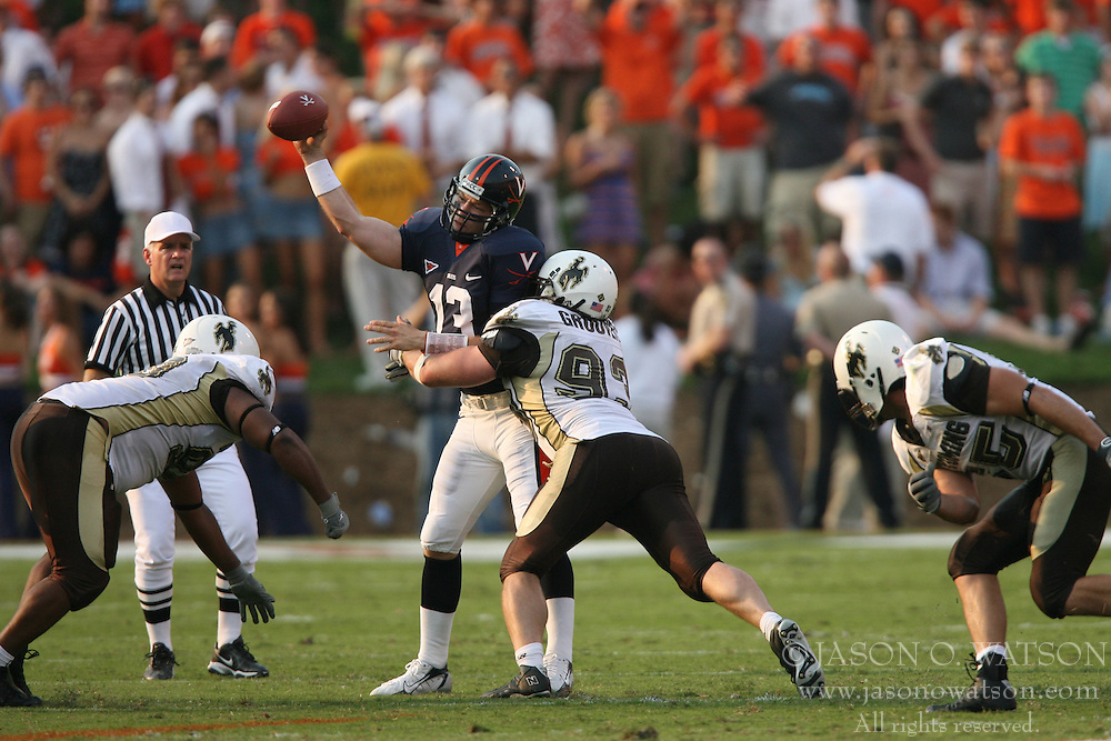 Virginia quarterback Kevin McCabe (13) is hit by Wyoming defensive tackle Mike Groover (93) as he throws.  The Virginia Cavaliers defeated the Wyoming Broncos 13-12 in overtime on September 9, 2006 at Scott Stadium in Charlottesville, VA.