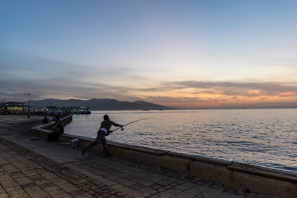 A Turkish man fishing at sunset in Izmir casts his line into the Aegean Sea. Izmir is one of Turkey's largest cities, and its largest on the Aegean coast. A ferry is docked in the background.