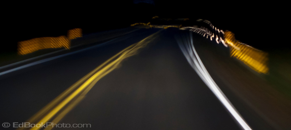 an abstract image of a curve in the road in the forest at night panoram