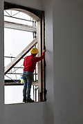 Worker balancing on a window while working. Building site