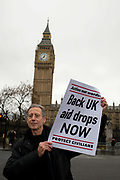 Whilst a small group demonstrate in Parliament Square urging the UK Government to drop aid to beseiged cities in Syria, Peter Tatchell, activist, stands in front of Big Ben holding a poster saying Back UK aid drops now on December 13th 2016 in London, UK.