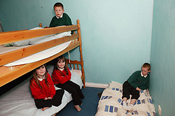 Young children sitting around in their bedroom,