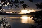 A strong evening sun sinks below storm clouds and Highland mountains at Loch Garry, Glengarry, Scotland. .