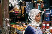 A woman walks through a market wearing a scarf, Baghdad, Iraq