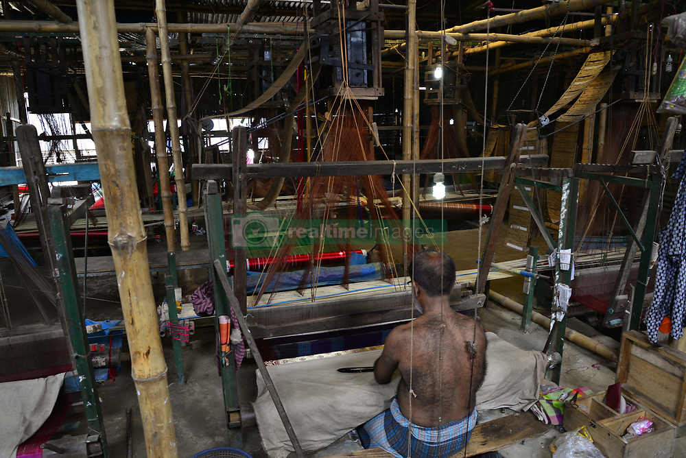 June 4, 2017 - Dhaka, Bangladesh - Bangladeshi weaver weaves Benarasi sari (Woman Wear) on a traditional wooden hand weaving loom at Mirpur in Dhaka, Bangladesh. On June 05, 2017.Benarasi Sari has an ancient history beginning from the Mughal Empire in the 16th century. It is known that it originated from Benaras, a northern city of India. Benarasi Sari found its way to Bangladesh, when the Muslims migrated from Benaras into Bangladesh. It was these migrants that started the practice of making Benarasi Sari at Mohammadpur and Mirpur in Dhaka.The texture of a Benarasi fabric can be either light or heavy. The silk is first put into rollers that twist a single silk thread with another to thicken its texture. This is then heated and put into a Tana where it is made into a bundle. The threads are then dyed elsewhere. The threads are stretched out in a single room made of rusted tin and worn out bamboo with barely any ventilation or lighting. In another similar room, a weaver weaves the designs on a sari. A single Benarasi Sari that is 21 feet in length and 3.5 feet in breadth can take a week or longer to be completed. (Credit Image: © Str/NurPhoto via ZUMA Press)