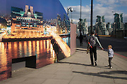 A young boy looks over his shoulder by a construction hoarding, a night time panorama of the Thames south bank, featuring the HQ of the intelligence service (MI6) across the river in Vauxhall.