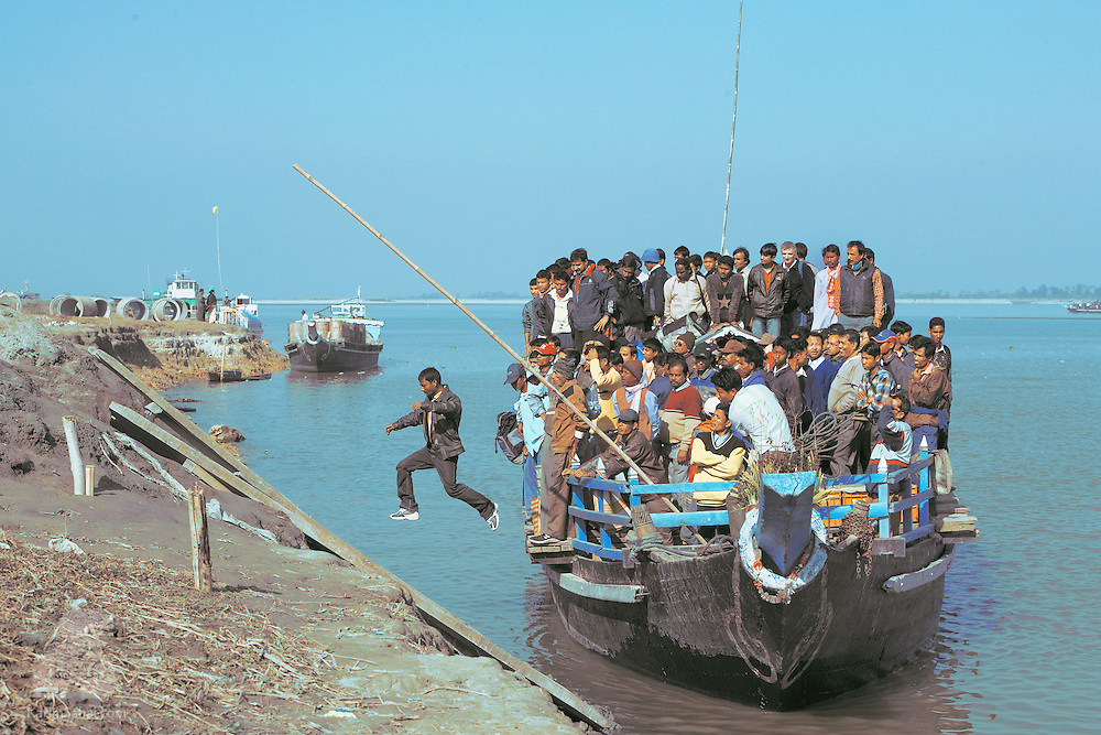 A man jumps off the fully loaded Majuli island ferry. Majuli is the largest sand river island in the world and lies in the middle of the Bhramaputra, one of the major waterways of India.