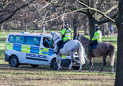 © Licensed to London News Pictures. 22/01/2021. London, UK. Police officers in a van and on horseback patrol Hyde Park this afternoon. Police patrol a busy Hyde Park in London as members of the public enjoy a walk in the sunshine. Today, Prime Minister Boris Johnson will address the nation at a 5pm Downing Street press briefing as the government downplays the idea of a universal £500 covid payment for those who self-isolate. A leaked government document suggested giving £500 to anyone who tested positive for coronavirus as death rates continue to rise in England. Photo credit: Alex Lentati/LNP