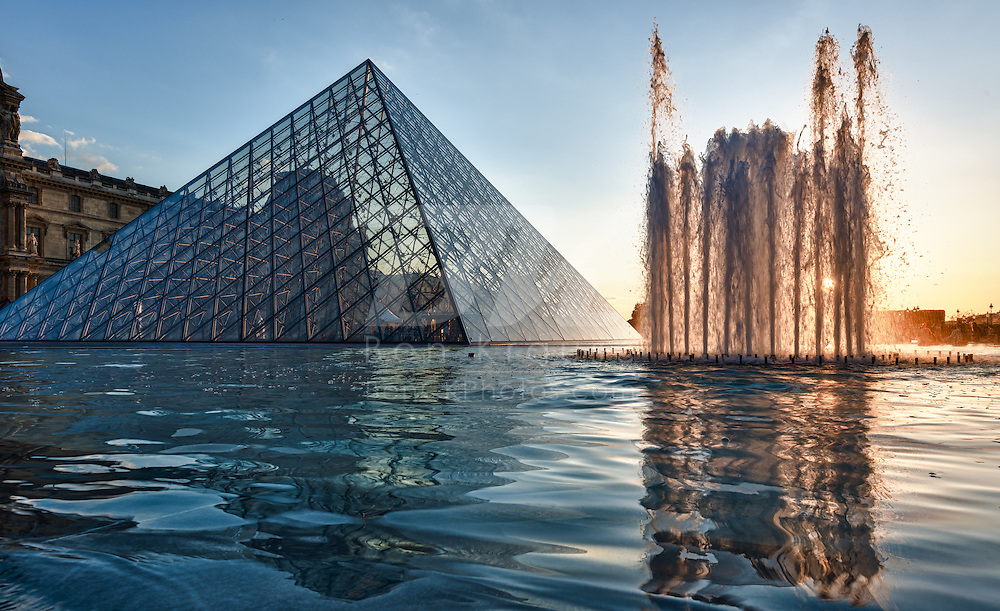A high dynamic range photo of the sun setting behind Musée du Louvre in Paris, France on May 16, 2012.