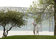Beacon, New York - A man lifts up a little girl while a boy watches at a Hudson River waterfront park on May 1, 2010. The Newburgh Beacon Bridge is in the background.