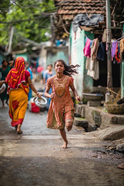 A young woman wearing a pretty dress running barefoot through an alleyway, Tangra slum, Dhipi, Kolkata, India