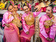 "14 JANUARY 2015 - BANGKOK, THAILAND: Girls in traditional attire pose for a ""selfie"" before the 2015 Discover Thainess parade. The Tourism Authority of Thailand (TAT) sponsored the opening ceremony of the ""2015 Discover Thainess"" Campaign with a 3.5-kilometre parade through central Bangkok. The parade featured cultural shows from several parts of Thailand. Part of the ""2015 Discover Thainess"" campaign is a showcase of Thailand's culture and natural heritage and is divided into five categories that match the major regions of Thailand – Central Region, North, Northeast, East and South.     PHOTO BY JACK KURTZ"