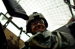 A rain soaked Humvee gunner with Charlie Co. 1-26 Infantry 1st Infantry Division looks down from his turret during a patrol through Adhamiya on Thursday April 27, 2007.