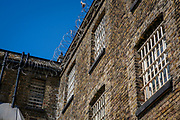 Barred cell windows and razor wire in HM Prison Wandsworth is a Category B men's prison at Wandsworth in the London Borough of Wandsworth, South West London, United Kingdom. It is operated by Her Majesty's Prison Service and is one of the  largest prisons in the UK with a population over 1500 people. (photo by Andy Aitchison)