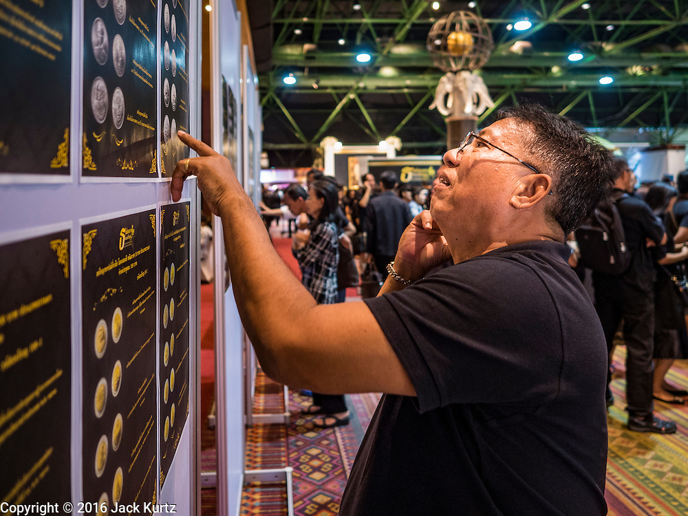 22 DECEMBER 2016 - BANGKOK, THAILAND: A man looks at a graphic of commemorative coins honoring the late King at Queen Sirikit Convention Center. The Thai treasury department sold commemorative coins to honor Bhumibol Adulyadej, the Late King of Thailand, at Queen Sirikit Convention Center in Bangkok. Thecoins celebrate milestones in the beloved monarch's life. PHOTO BY JACK KURTZ