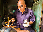 "19 AUGUST 2013 - BANGKOK, THAILAND:     A craftsman solders the seams on a monk's bowl, called ""bat"" (pronounced with a long ""a"" as in baat) on Soi Baan Bat in Bangkok. The bowls are made from eight separate pieces of metal said to represent the Buddha's Eightfold Path. The Monk's Bowl Village on Soi Ban Baat in Bangkok is the only surviving one of what were originally three artisan's communities established by Thai King Rama I for the purpose of handcrafting ""baat"" the ceremonial bowls used by monks as they collect their morning alms. Most monks now use cheaper factory made bowls and the old tradition is dying out. Only six or seven families on Soi Ban Baat still make the bowls by hand. Most of the bowls are now sold to tourists who find their way to hidden alleys in old Bangkok. The small family workshops are only a part of the ""Monk's Bowl Village."" It is also a thriving residential community of narrow alleyways and sidewalks.  PHOTO BY JACK KURTZ"