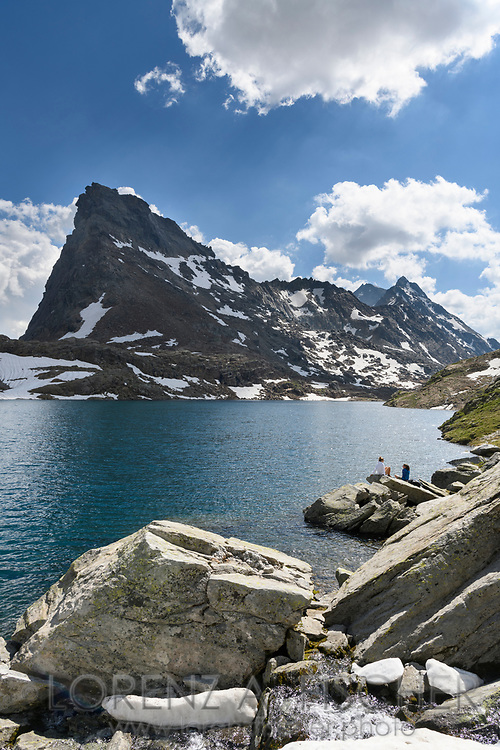 Two female hikers are resting at the lake Geisspfadsee with the peaks of the Rothorn and the Schwarzhorn, Landschaftspark Binntal, Valais, Switzerland