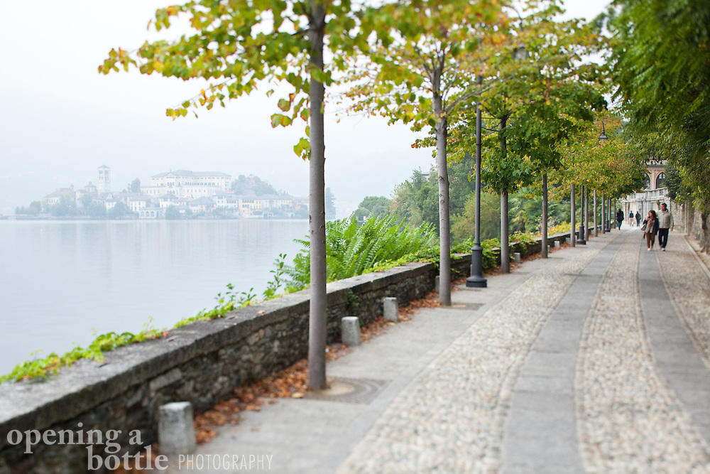 A couple walks along the road into Orta San Giulio on Lake Orta, with Isola San Giulio in the distance, Piedmont, Italy.