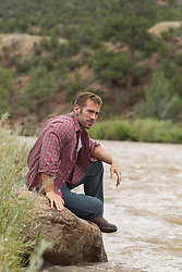 man sitting on a rock by a river