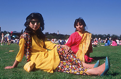Two teenage girls wearing traditional dress sitting on grass at music festival,