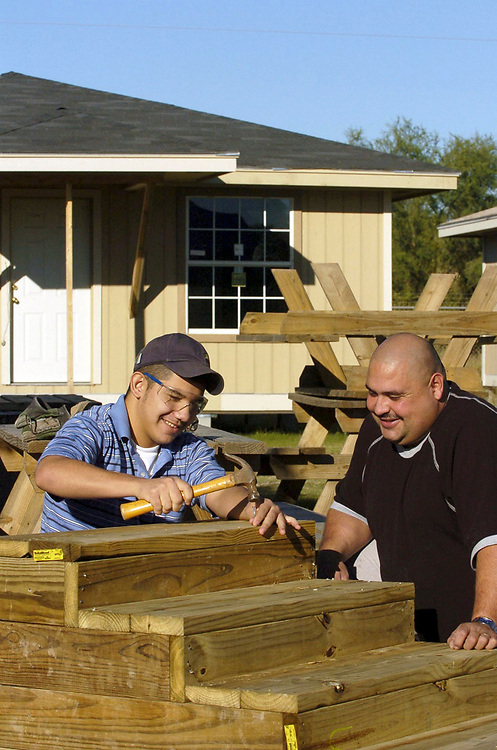 San Juan, TX 17DEC04: Hispanic father and 15 year old son work on stairs for new house in volunteer housing project. They purchased a home through Proyecto Azteca, a low-income housing assistance project where families contribute time in exchange for purchasing a low-cost house. Model Released. <br /> ©Bob Daemmrich/