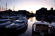 Wealthy boats and yachts at sunset moored at St Katherine Dock, London.