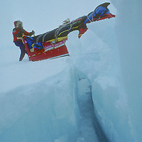 Expedition dog team crosses fractured pressure ridge on frozen Arctic Ocean.
