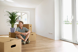 Man sitting floor looking new apartment happy