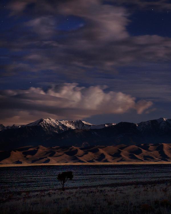 The rising moon illuminates the Great Sand Dunes.