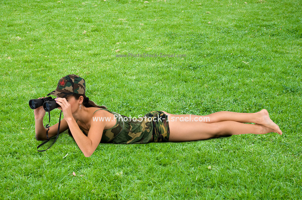 young woman in sexy military uniform with binoculars