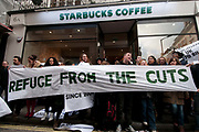 Conduit Street off Regent Street. UK Uncut flashmob occupy Starbucks to draw attention to the fact that they have paid no corporation tax for the last three years, and that the tax that rich companies haven't paid, would pay for the cuts the government is making to public services. Women hold a banner saying 'Refuge from the cuts'.