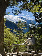 A hiker rests on a bench admiring water falling from an ice cap in Rob Roy Valley, Mount Aspiring National Park, Southern Alps, South Island, New Zealand. (Self portrait.) In 1990, UNESCO honored Te Wahipounamu - South West New Zealand as a World Heritage Area.