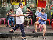 11 SEPTEMBER 2013 - BANGKOK, THAILAND:  The proprietor of a street side curry stand in the Chinatown section of Bangkok carries an order to a customer. Thailand in general, and Bangkok in particular, has a vibrant tradition of street food and eating on the run. In recent years, Bangkok's street food has become something of an international landmark and is being written about in glossy travel magazines and in the pages of the New York Times.        PHOTO BY JACK KURTZ