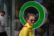 A woman in yellow and wearing round sunglasses walks past one of the green cirlces outside M&Ms Worlds Leicester Square store, on 31st July 2017, in London, England.