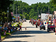 04 JULY 2020 - RUNNELLS, IOWA: The 4th of July tractor parade goes through downtown Runnells, a small community about 25 miles from Des Moines. Most of the Independence Day parades in central Iowa were cancelled because of the COVID-19 (Coronavirus) pandemic. People in Runnells made the decision to go ahead with their parade, the first 4th of July parade in the town in recent memory. Most of the people in the parade were farmers, who drove their tractors through the town.     PHOTO BY JACK KURTZ