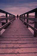 Young teen female walking across a footbridge in Walberswick in Suffolk
