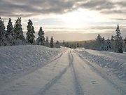 A snowy backroad through the forest on 19th February 2020 in Finnish Lapland. The natural features and landscape of the fells have always enchanted hikers and the area offers magnificent fells and seemingly endless woodlands.