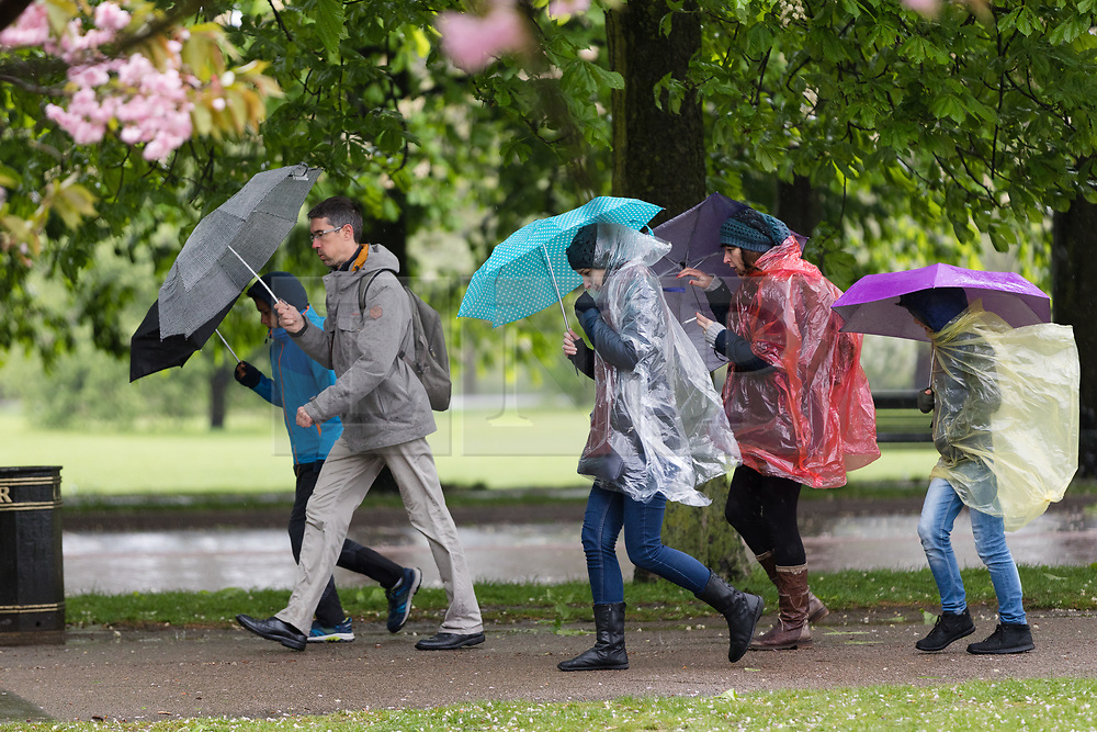 © Licensed to London News Pictures. 30/04/2018. London, UK. People with umbrellas and rain ponchos walk through Greenwich Park in London during wet and windy weather. The capital has been experiencing heavy rain and windy weather today. Photo credit: Vickie Flores/LNP
