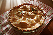 Homemade apple pie with clover decoration  in the crust sitting on a kitchen towel on a table with sunlight falling across it.
