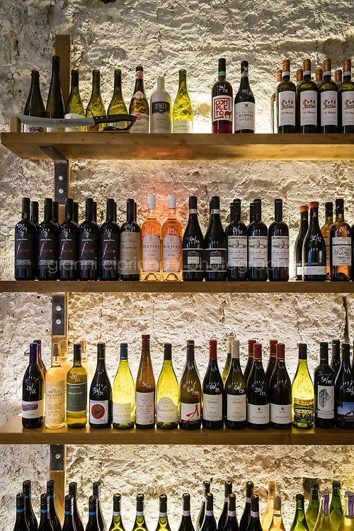 NAPLES, ITALY - 23 OCTOBER 2020: Wine bottles are seen here on display at the Vineria Bandita, a wine bar in the Vomero district in Naples, Italy, on October 23rd 2020.<br /> <br /> Vineria Bandita, managed by Giuliano Granata together with his partner Federica Palumbo, is mainly - but not only - dedicated to the so called 'artisanal' wines, as well as to the enhancement of the work of small producers.