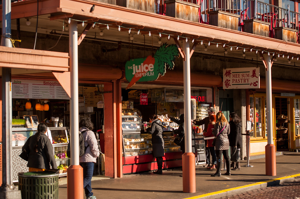 2017 DECEMBER 05 - People walk past Mee Sum Pastry and The Juice Emporium, at Pike Place Market, Seattle, WA, USA. By Richard Walker