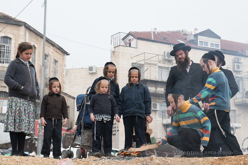 Jerusalem, Israel. 30th March, 2018. A group of people watching how a kid starts a bonfire for burning leavened food during the morning of Pesach at Mea Shearim neighborhood. © Valentin Sama-Rojo.