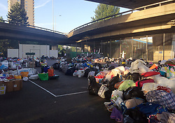 Tennis courts at the Westway Sports Centre close to the scene which are overflowing with provisions after a fire engulfed the 24-storey Grenfell Tower in west London yesterday.