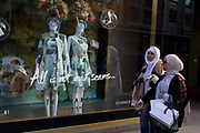 Two Muslim women walk past a display of eccentric mannequins in diving masks and snorkels, outside a central London branch of Ted Baker. In an image of a western and eastern culture clash, we see the ladies wearing scarves and hejabs in keeping with their own styles of dress while in the background are two mannequins in floral printed dresses, tall hairdos and weirdly, diving masks and snorkels. The shop is Ted Baker plc, a British luxury clothing retail company. It is listed on the London Stock Exchange and is a constituent of the FTSE 250 Index. Its founder and CEO, Ray Kelvin, started his first store in March 1988 and it now has stores and outlets in the rest of Europe, United States of America, Canada, Australia, Asia, China and the Middle East.