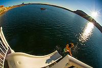 Woman going off a waterslide aboard a 75 foot luxury-class houseboat on Lake Powell, Glen Canyon National Recreation Area, Arizona/Utah border USA