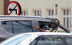 HARARE, ZIMBABWE - NOVEMBER 15 : A soldier guides a vehicle as they sealed off a main road to the parliament building within the military activities taking place in Harare, Zimbabwe on November 15, 2017. President Robert Mugabe and his family have been detained following military intervention in capital Harare, which an army spokesman and the ruling party insisted Wednesday was &