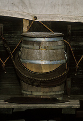 wooden barrel secured to the side of a western covered wagon