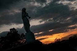 """Der Metairie Cemetery ist ein ländlicher Friedhof in New Orleans, Louisiana, USA. Der Name laesst faelschlicherweise vermuten, dass sich der Friedhof in Metairie, Louisiana, befindet. Er befindet sich jedoch innerhalb der Stadtgrenzen von New Orleans an der Metairie Road. Diese Grabstaette war zuvor eine Pferderennbahn, des 1838 gegründeten Metairie Race Course. Auf der Rennstrecke fand am 1. April 1854 das berühmte Lexington-Lecomte-Rennen statt, das als """"Norden gegen den Süden"""" -Rennen bezeichnet wurde. Der frühere Praesident Millard Fillmore war anwesend. Wegen des amerikanischen Bürgerkriegs wurde das Rennen eingestellt und als konfoederiertes Lager (Camp Moore) genutzt, bis David Farragut im April 1862 New Orleans für die Union einnahm. Der Metairie Cemetery wurde danach auf dem Gelände des alten Metairie Race Course errichtet. Im Bild ein Sonnenuntergang und eine Engelsstatue, aufgenommen am 15.02.2020, New Orleans, Vereinigte Staaten von Amerika // Metairie Cemetery is a rural cemetery in New Orleans, Louisiana, United States. The name has caused some people to mistakenly presume that the cemetery is located in Metairie, Louisiana; but it is located within the New Orleans city limits, on Metairie Road (and formerly on the banks of the since filled-in Bayou Metairie). This site was previously a horse racing track, Metairie Race Course, founded in 1838. The race track was the site of the famous Lexington-Lecomte Race, April 1, 1854, billed as the """"North against the South"""" race. Former President Millard Fillmore attended. While racing was suspended because of the American Civil War, it was used as a Confederate Camp (Camp Moore) until David Farragut took New Orleans for the Union in April 1862. Metairie Cemetery was built upon the grounds of the old Metairie Race Course after it went bankrupt. The race track, which was owned by the Metairie Jockey Club, refused membership to Charles T. Howard, a local resident who had gained his wealth by starting the fi"""