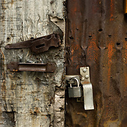 Metal sliding door on a workshop in Ashland, Oregon.  The door and building have seen better days.  The door and sliding has been dented many times and siding is covered with rust.