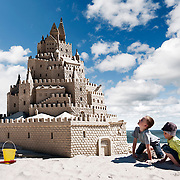 Two young boys admiring their handiwork of a very impressive sandcastle on the beach.